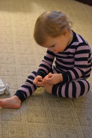 Picking her toe jam.